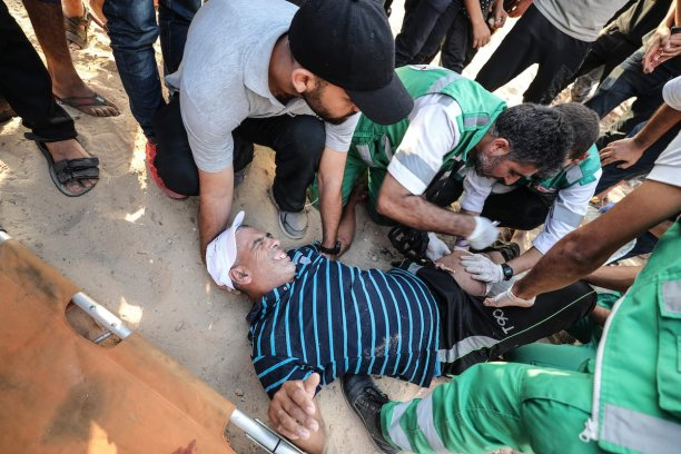 """GAZA CITY, GAZA - OCTOBER 8: Health team members treat a wounded Palestinian due to Israeli forces' intervention during the """"maritime demonstration"""" to break the Gaza blockade by sea with more than 20 vessels of various sizes in Gaza City, Gaza on October 8, 2018. ( Mustafa Hassona - Anadolu Agency )"""