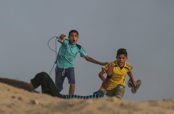 """GAZA CITY, GAZA - OCTOBER 8: Palestinian kids run to help a wounded protester during the """"maritime demonstration"""" to break the Gaza blockade by sea with more than 20 vessels of various sizes in Gaza City, Gaza on October 8, 2018. ( Mustafa Hassona - Anadolu Agency )"""