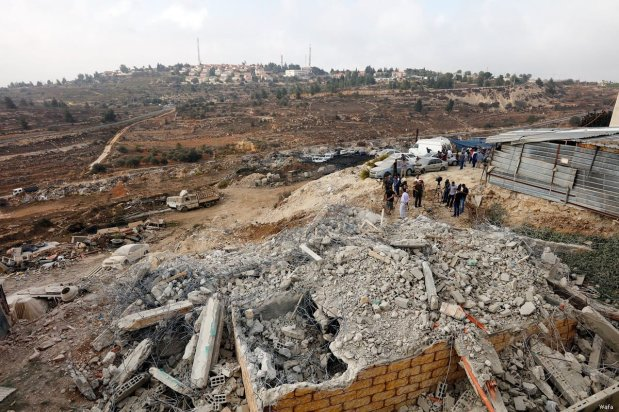 Palestinians look at rubble left behind after Israeli forces demolished Palestinian owned buildings on 18 October 2018 [Wafa]