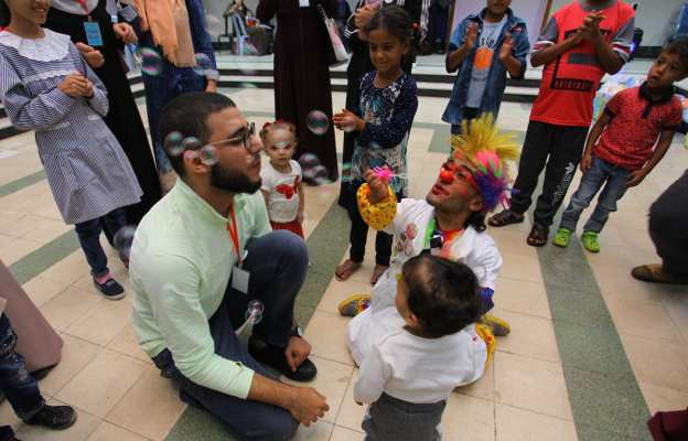 Palestinian clowns play with children with cancer at el-Rantisi hospital in Gaza city, on 7 October 2018. [Mahmoud Ajjour/Apaimages]