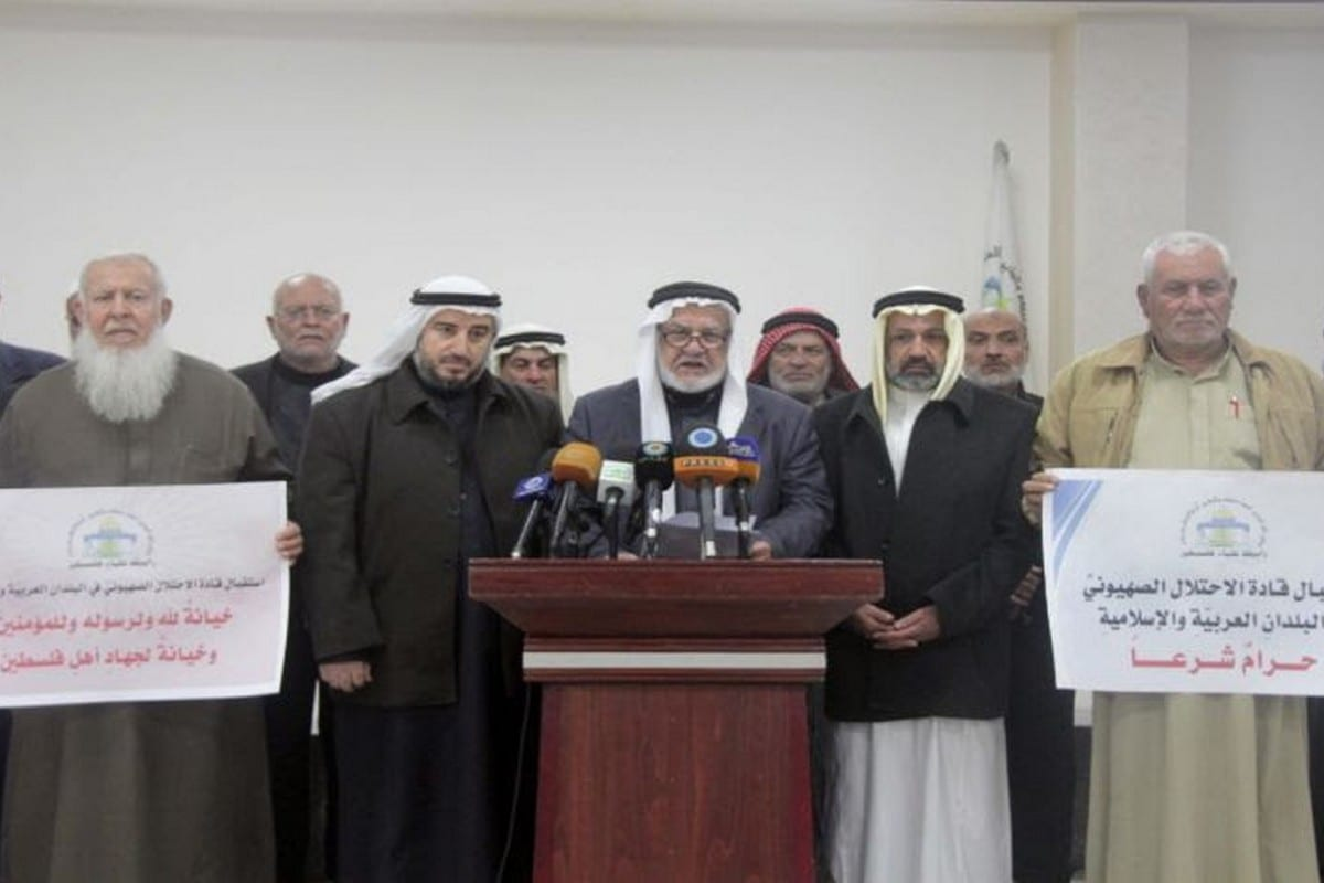 Palestinian Union of Religious Scholars carry sings reading 'Receiving the leaders of the occupation in Arab countries is a betrayal to the resistance of the Palestinians.'