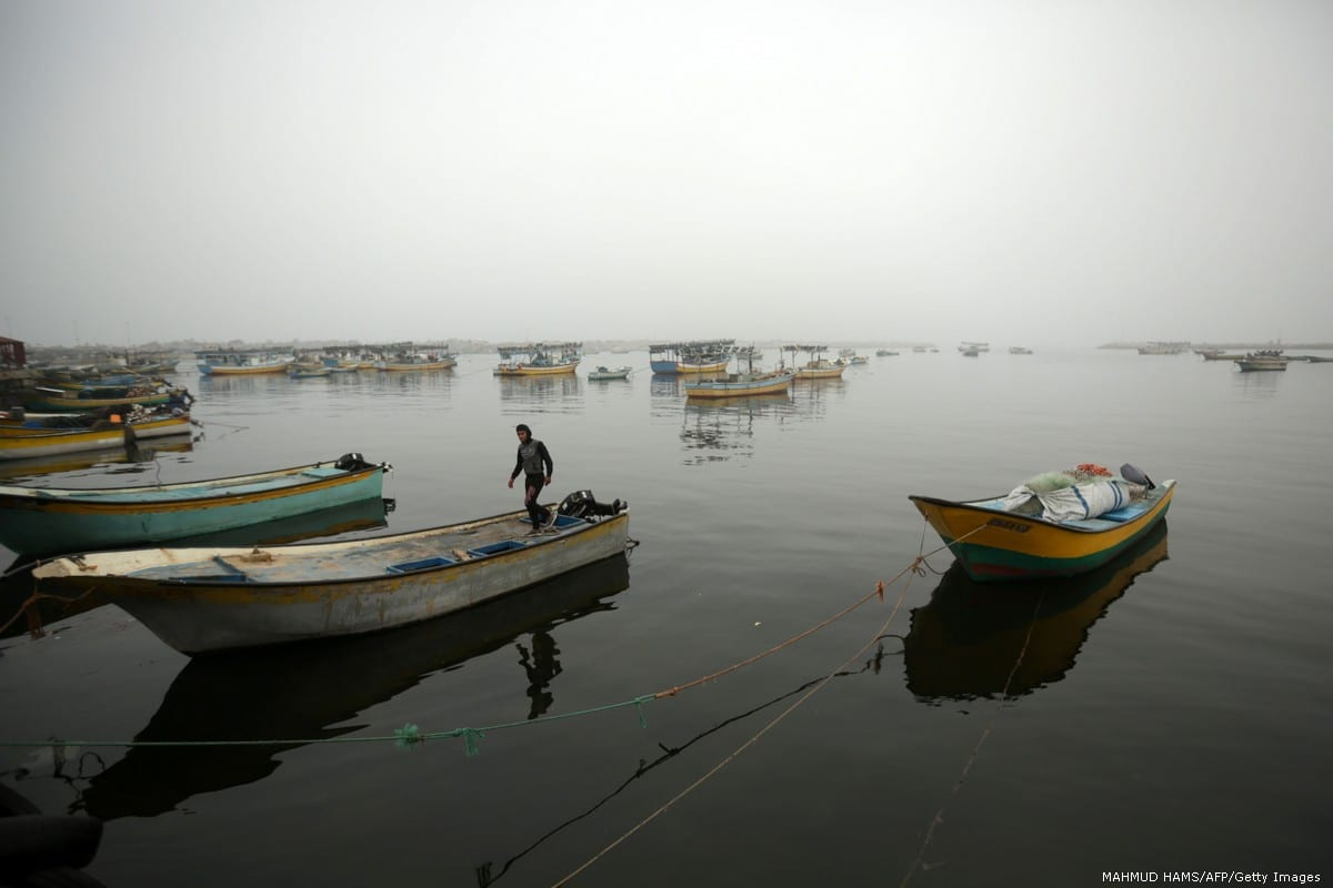 A Palestinian fisherman stands on his boat in Gaza City on 26 February 2017 [MAHMUD HAMS/AFP/Getty Images]