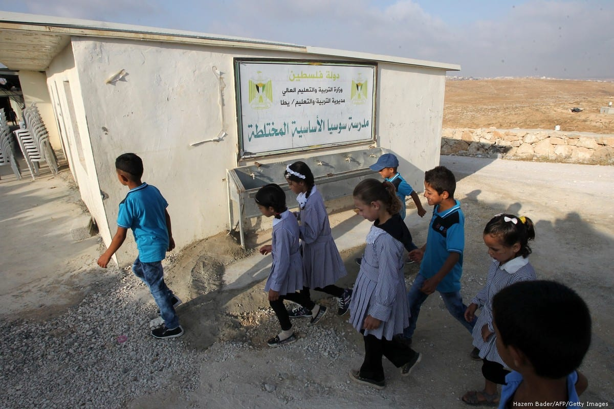 Palestinian boys and girls arrive at the school in the occupied West Bank city of Hebron [Hazem Bader/AFP/Getty Images]