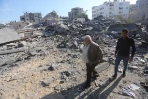 Two men walk through the rubble in the aftermath of Israel's deadly air strike last night. 13 November 2018 [Mohammed Asad/Middle East Monitor]