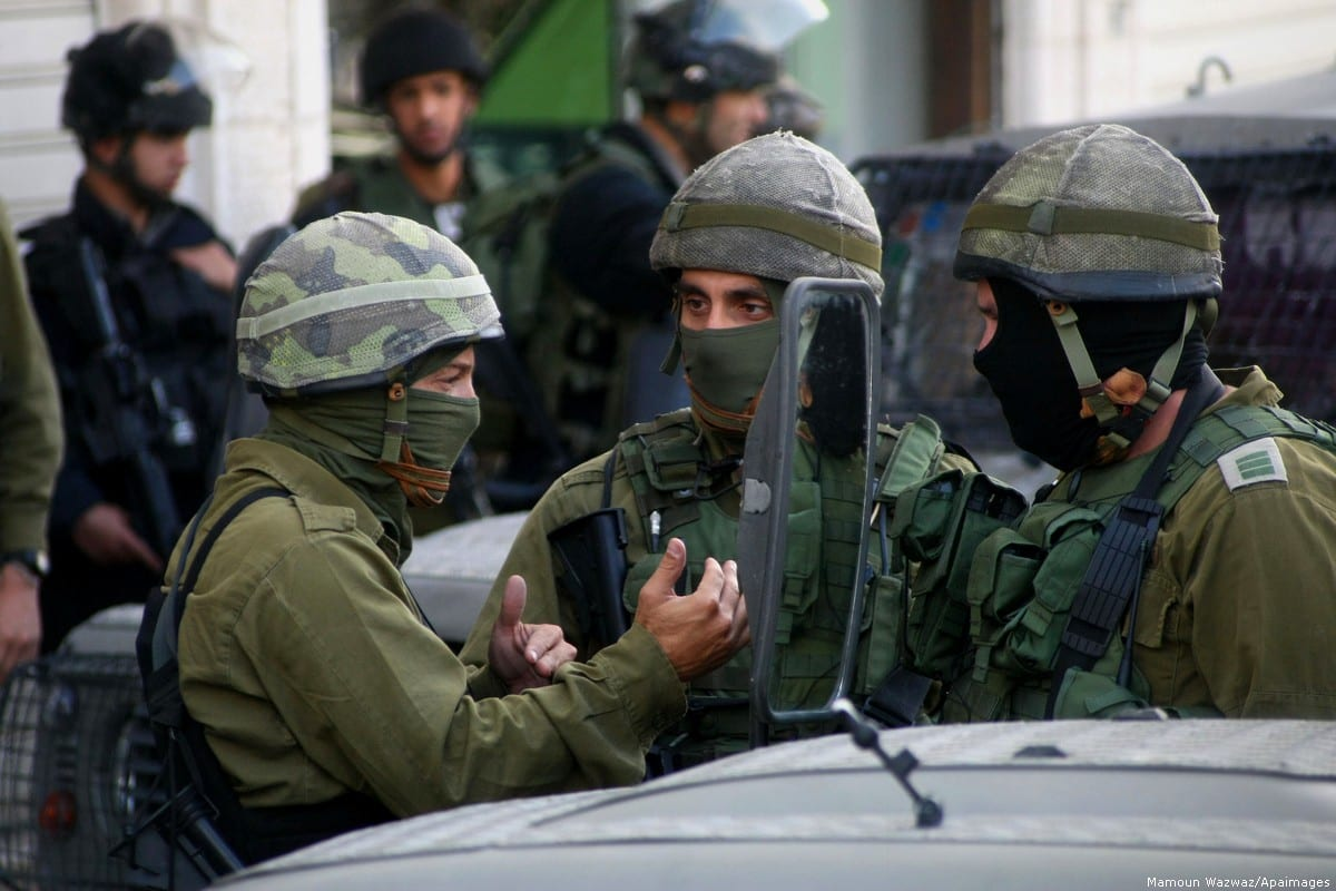 Israeli soldiers stand guard at a checkpoint in the West Bank town of Hebron on June 16, 2014. [Mamoun Wazwaz/Apaimages]