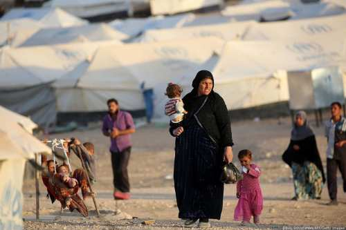 A woman walks with children at a refugee camp on October 17, 2016 [DELIL SOULEIMAN/AFP/Getty Images]