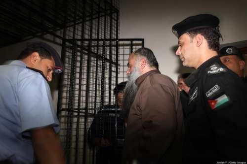 A prisoner is escorted to his cell on September 24, 2014 in, Jordan. [Jordan Pix/ Getty Images]