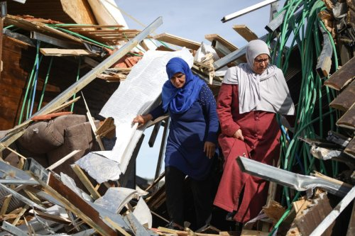 Palestinian Maghribi family collect their belongings amid ruins of their house after Israeli authorities demolished the top part of it in Jabal Al-Mukaber of East Jerusalem on 28 November, 2018 [Mostafa Alkharouf/Anadolu Agency]