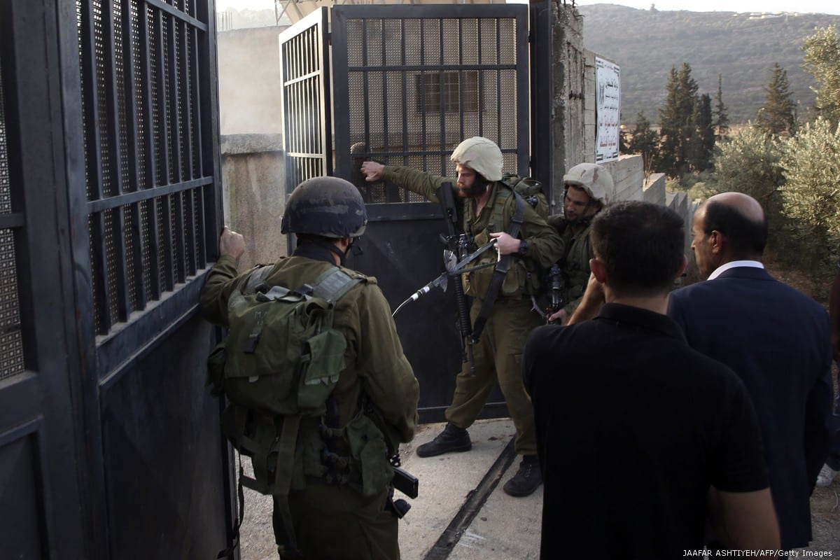 Members of the Israeli security forces gather at the main entrance of a Palestinian school in the West Bank on 15 October 2018 [JAAFAR ASHTIYEH/AFP/Getty Images]