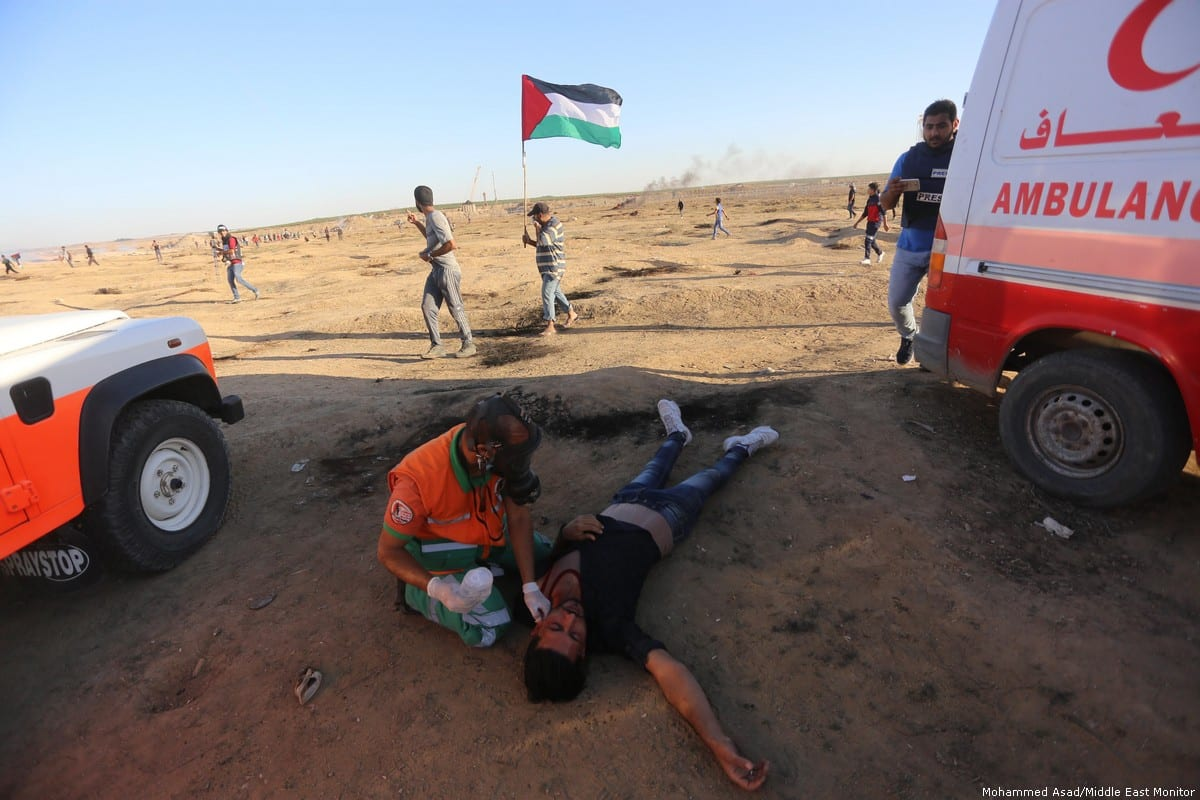 A paramedic attends to an injured Palestinian who was hurt after Israeli forces attacked protesters at the Gaza-Israel border during the Great March of Return on 2 November 2018 [Middle East Monitor/Middle East Monitor]