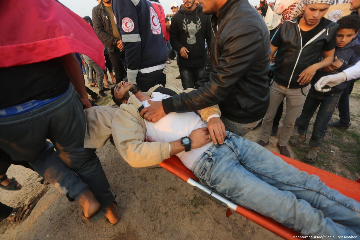 An injured Palestinian is put on a stretcher after Israeli forces fired at Palestinians during the Great March of Return on 30 November 2018 [Mohammed Asad/Middle East Monitor]