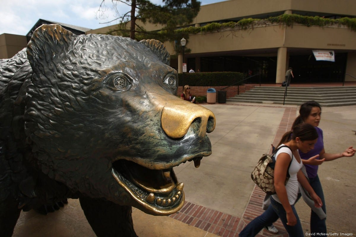 Students pass the bronze statue of their campus mascot, The Bruin, a California grizzly bear, at University of California, Los Angeles (UCLA) on 28 May 2018 [David McNew/Getty Images]