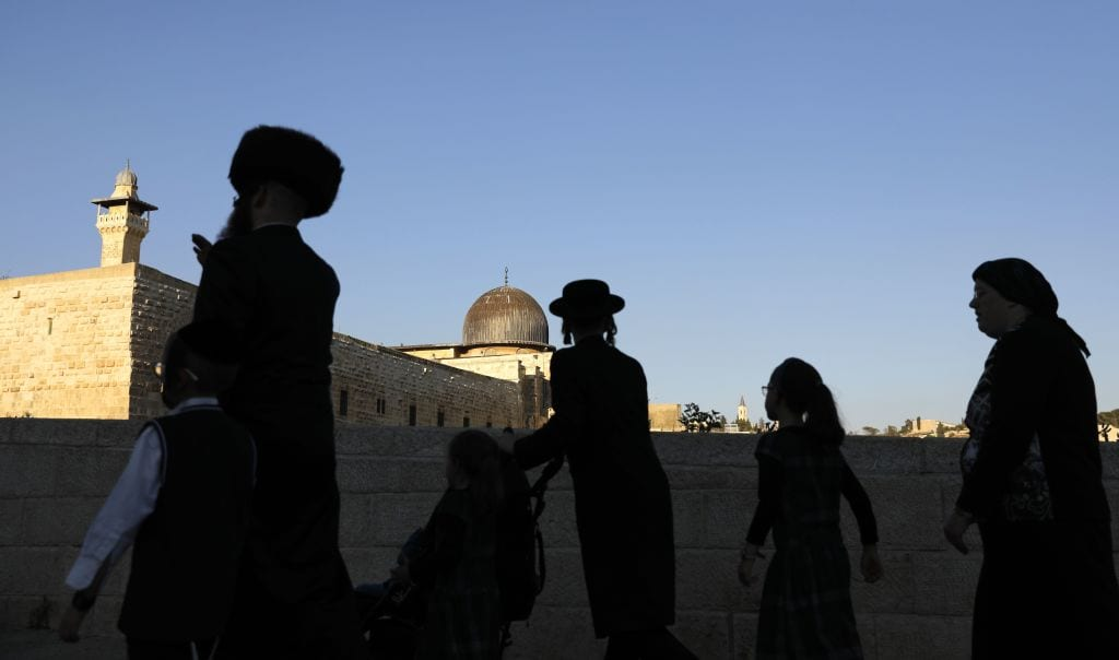 Members of an Ultra-Orthodox Jewish family walk at the Jewish quarter in Jerusalem's Old City overlooking al-Aqsa Mosque on September 27, 2018 - (Photo by AHMAD GHARABLI/AFP/Getty Images)