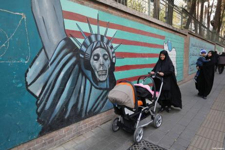 Iranian women walk past landmark graffiti on the walls of the former US embassy in Tehran during a protest on November 4, 2018, marking the anniversary of its storming by student protesters that triggered a hostage crisis in 1979 [ATTA KENARE/AFP/Getty Images]