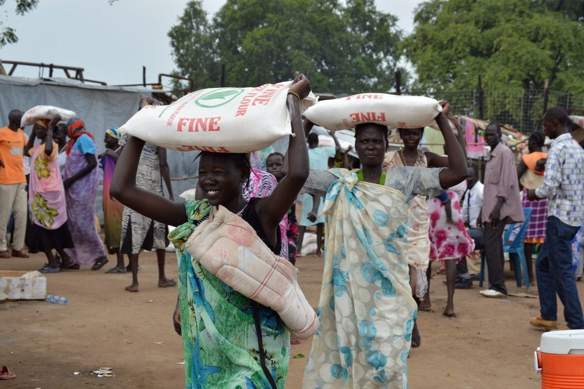 Women carry flour sacks during a food distribution by the Catholic Church to refugees and displaced people in Juba on August 30, 2014 [SAMIR BOL/AFP/Getty Images]
