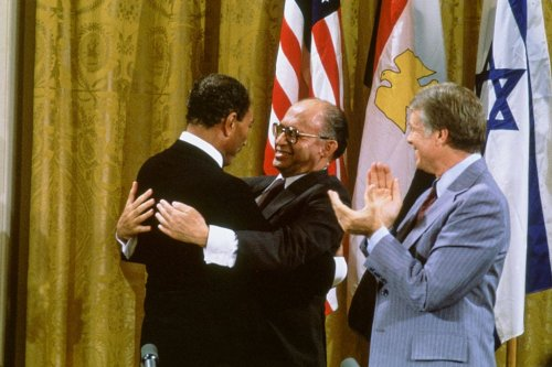 Egyptian President Anwar al-Sadat and Israeli Premier Menachem Begin embrace, while US President Jimmy Carter applauds after signing the Camp David Accords in the East Room of the White House, September 18, 1978, in Washington, DC. [David Hume Kennerly/Getty Images]