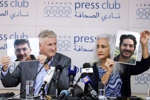 Marc (L) and Debra Tice, parents of US journalist Austin Tice who was kidnapped in Syria five years prior, hold respective dated portraits of him during a press conference in the Lebanese capital Beirut on 20 July 2017. [Photo by JOSEPH EID / AFP / Getty Images]