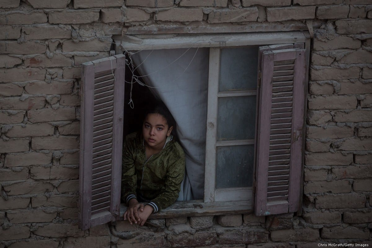 A young girl looks out of her window in Cairo, Egypt on 10 December 2016 [Chris McGrath/Getty Images]