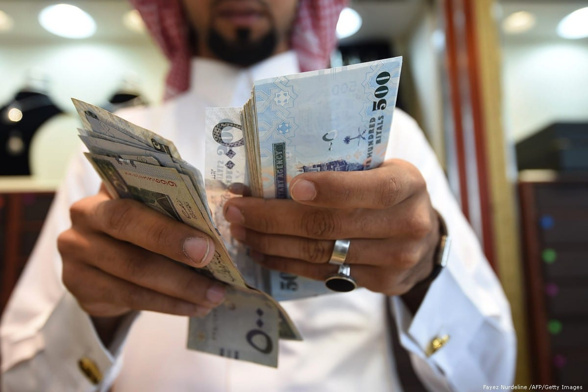 A man counts Saudi riyal banknotes at a market in Riyadh, Saudi Arabia on 3 October 2016 [Fayez Nurdeline /AFP/Getty Images]