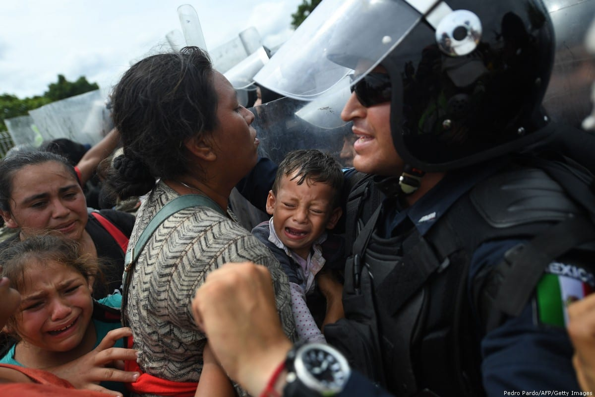 Honduran migrants heading in a caravan to the US, holding up a crying baby while they struggle to cross one of the gates of the Guatemala-Mexico international border bridge in Ciudad Hidalgo, Chiapas state, Mexico, on 19 October, 2018 [PEDRO PARDO/AFP/Getty Images]