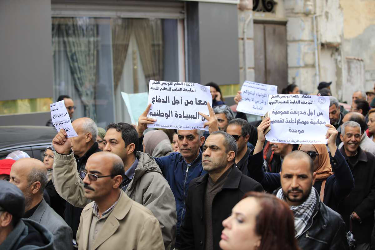 High school and secondary school teachers stage a demonstration demanding wage increase, early retirement and education reform in front of the Tunisian General Labour Union building as they march to the Habib Burgiba Avenue in Tunis, Tunisia on 12 December 2018. [Nacer Talel/Anadolu Agency]
