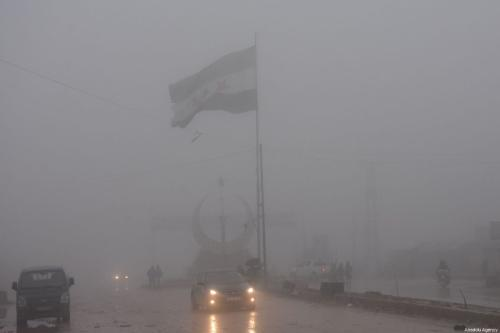 A vehicle drives along a road as Syrian flag is seen barely on the background due to heavy fog and rainfall in Azez district in Aleppo on December 19, 2018. ( Samer Owaid - Anadolu Agency )