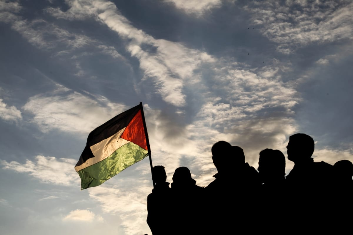 """A Palestinian holds a Palestinian flag during a protest within the """"Great March of Return"""" demonstrations on the Israel-Gaza border near Jabalia Refugee Camp in Gaza City, Gaza on December 21, 2018. ( Ramez habboub - Anadolu Agency )"""