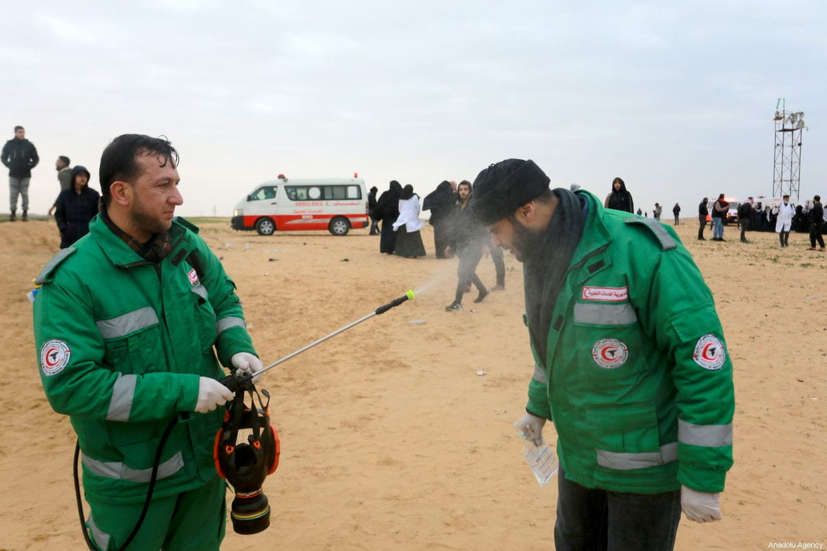 A Palestinian medic receives medical treatment after being effected by tear gas, thrown by Israeli forces in Rafah, Gaza on 28 December 2018 [Abed Rahim Khatib/Anadolu Agency]