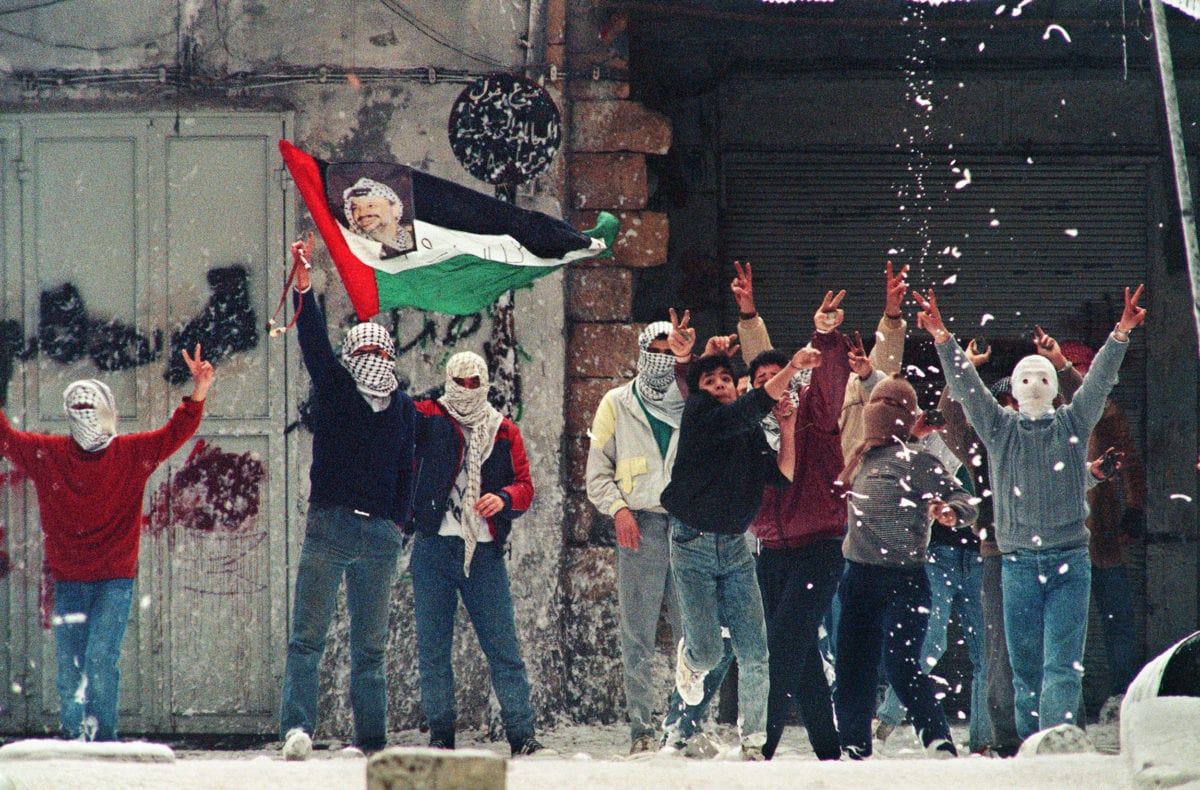 Several Palestinian demonstrators hold Palestinian flag with a portrait of PLO leader Yasser Arafat as foam thrown by Israeli soldiers drops from a roof during clashes 22 January 1988 in Nablus on the West Bank [SVEN NACKSTRAND/AFP/Getty Images]