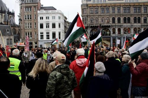 """People gather at Dam Square holding flags and banners during a demonstration organized by """"Palestinian House in Netherlands"""" Foundation, in support of Palestinian people, on December 30, 2018 in Amsterdam, Netherlands. The 'Return Key' monument, represents returning of Palestinians to their lands, was on display during the demonstration. ( Abdullah Aşıran - Anadolu Agency )"""