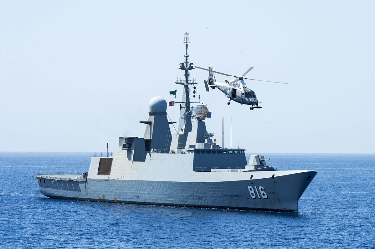 "The Royal Saudi Navy frigate Al Dammam (816) maneuvers into position, with its embarked AS565 SA Dauphin helicopter circling overhead, during exercise ""Eager Lion 2014"" in the Gulf of Aden on May 28, 2014 [US Navy / Public Domain]"