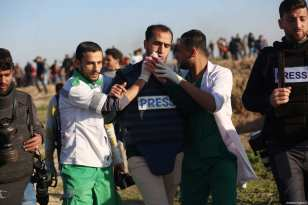"""A press member is being carried away after Israeli forces' intervention with tear gas during a protest within the """"Great March of Return"""" demonstrations at Al Bureij Refugee Camp near Gaza-Israel border in Gaza City, Gaza on January 11, 2019 [Hassan Jedi/Anadolu Agency]"""