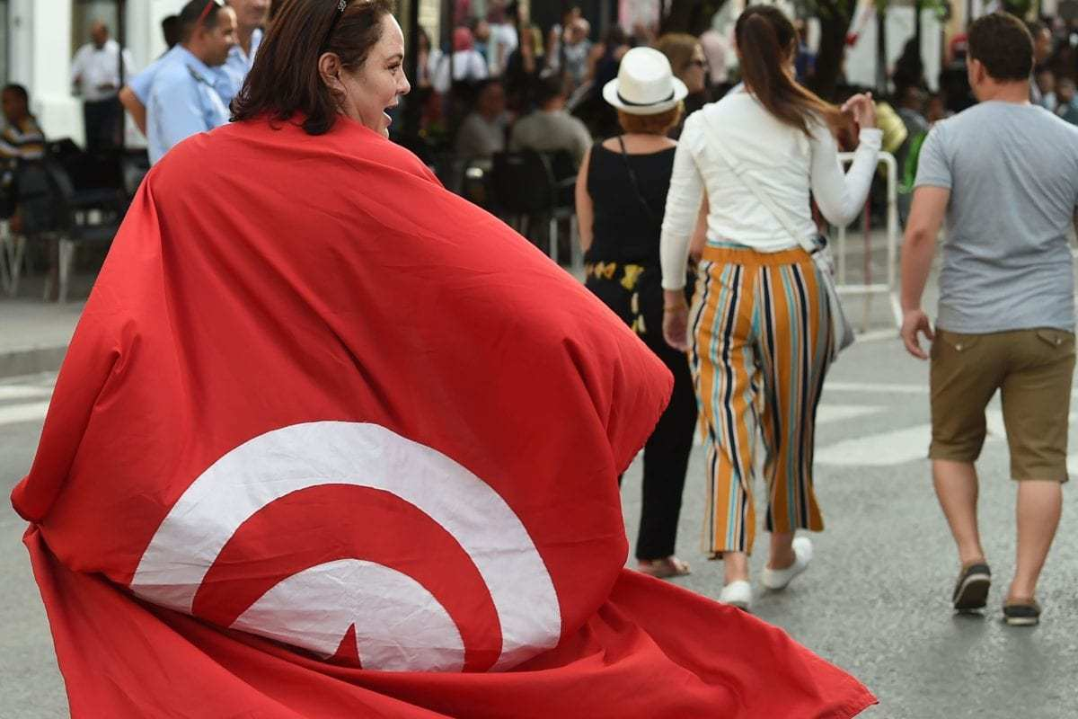 A Tunisians woman wears a national flag during a demonstration to mark Tunisia's Women's Day and to demand equal inheritance rights between men and women on August 13, 2018, in the capital Tunis [FETHI BELAID/AFP/Getty Images]
