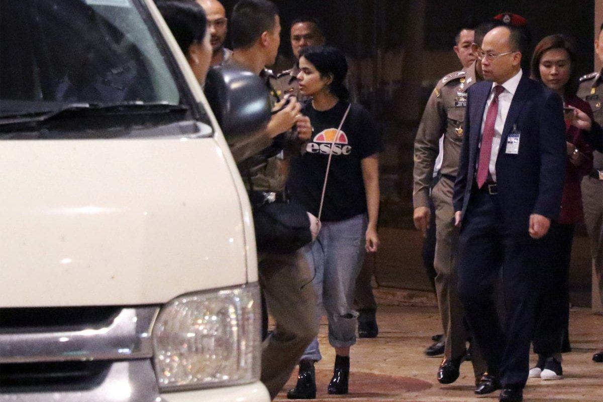 18-year-old Saudi woman Rahaf Mohammed al-Qanun (C) is escorted to a vehicle by a Thai immigration officer in Bangkok on 7 January 2019 [STR/AFP/Getty Images]