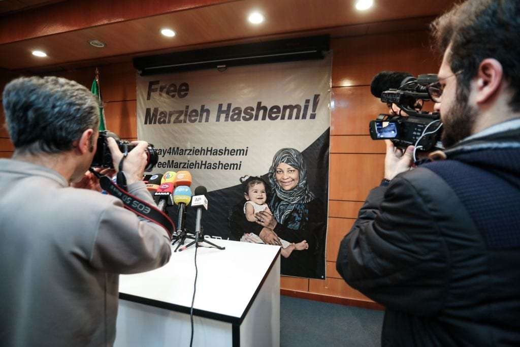 Journalists photograph and film a poster depicting US-born and US-based Iranian journalist Marzieh Hashemi, who was detained on unspecific charges upon arrival at St Louis Lambert International Airport, during a press conference by her employing organisation Press TV in the Iranian capital Tehran on 16 January 2019. [Photo by ATTA KENARE / AFP / Getty Images]