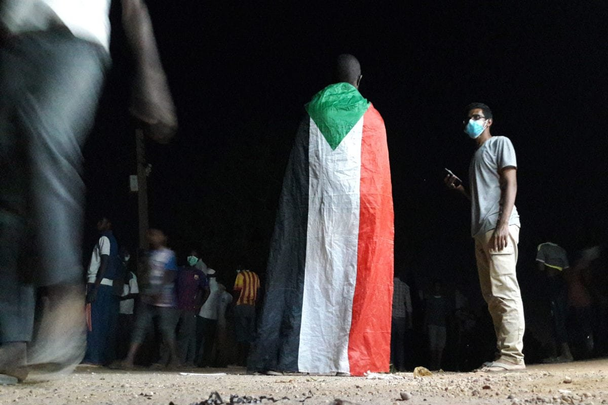 A Sudanese demonstrator wears the national flag during an anti-government protest in Khartoum, Sudan on 22 January 2019 [STRINGER/AFP/Getty Images]