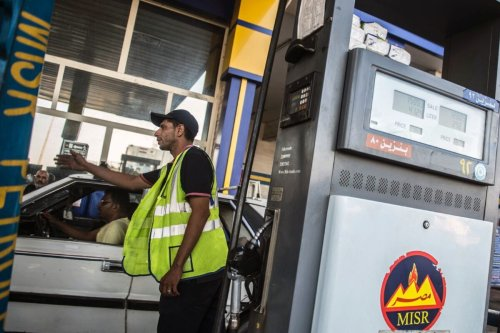 A worker gesturing for cars to move as others fill up a at a petrol station in Cairo, Egypt on June 29, 2017 [KHALED DESOUKI/Getty Images]