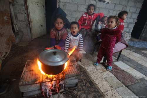 Gazans children stay warm during the winter months in Gaza on 21 January 2018 [Mohammed Asad/Middle East Monitor]