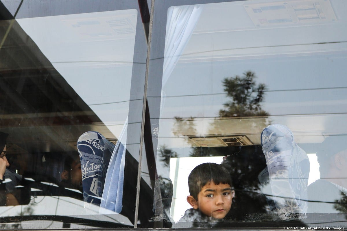 Syrian refugees evacuated from the southern Lebanese village of Shebaa ride a bus through the Masnaa crossing on the Lebanon-Syria border leading to Damascus on 18 April 2018 [HASSAN JARRAH/AFP/Getty Images]