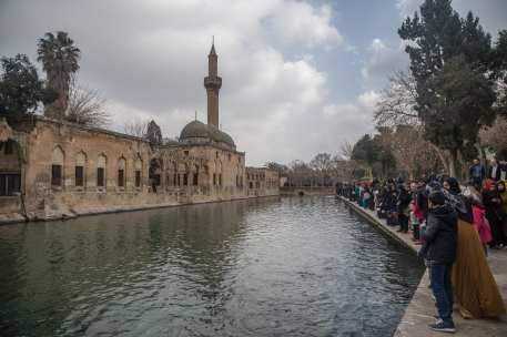 """People visit the ancient site and legendary the """"Pool of Sacred Fish"""" (Balikligol), also know as the """"Pool of Abraham"""" in Sanliurfa, Turkey on 26 January 2019 [Halil Fidan/Anadolu Agency]"""