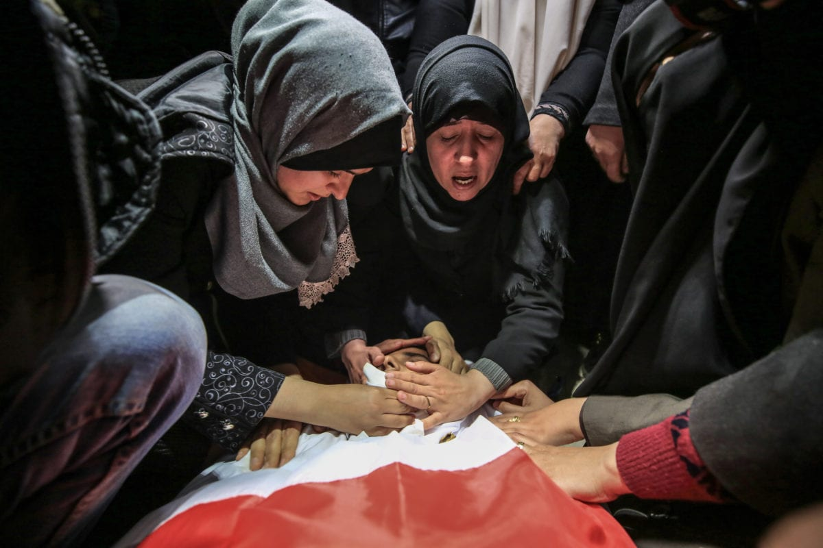 Relatives of 18-year-old Palestinian Hamza Muhammed Ishtiwi, mourn by his body during his funeral in Gaza City on February 9, 2019. [Ali Jadallah - Anadolu Agency ]