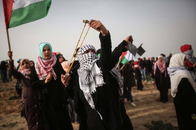 """Palestinian women use slingshot to throw stones to Israeli forces during clashes with Israeli forces' at a """"Great March of Return"""" demonstration near Al Bureij Refugee Camp in Gaza on February 15, 2019. ( Hassan Jedi - Anadolu Agency )"""