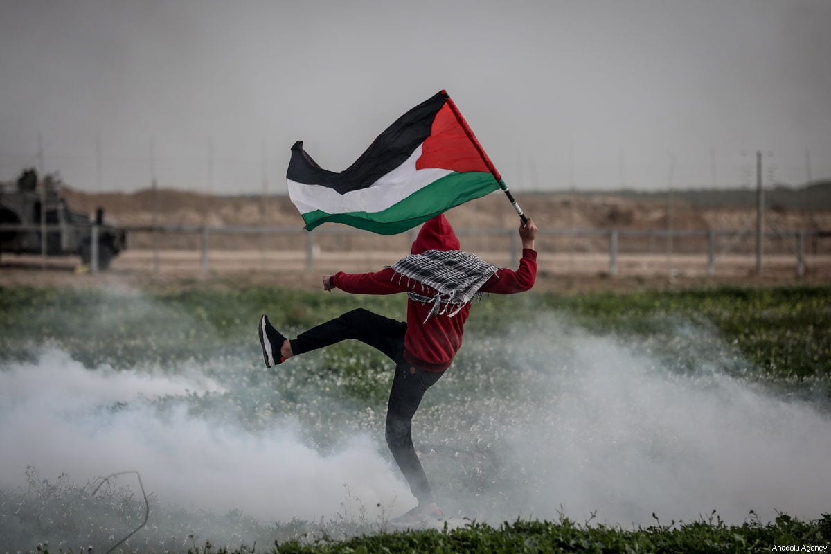 "A Palestinian is seen trying to kick-away a tear gas canister shot at him by Israeli forces, during a ""Great March of Return"" protest, in the Shuja'iyya neighbourhood of Gaza City, Gaza on February 15, 2019 [Ali Jadallah / Anadolu Agency]"