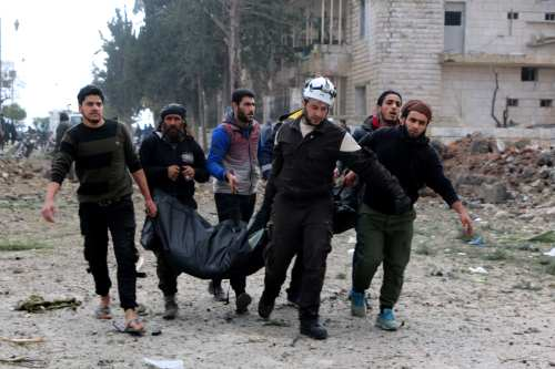 People carry body bag around the site after the consecutive bomb attacks with two bomb-laden vehicles in Idlib city centre, Syria on 18 February, 2019 [Ahmet Rehhal/Anadolu Agency]