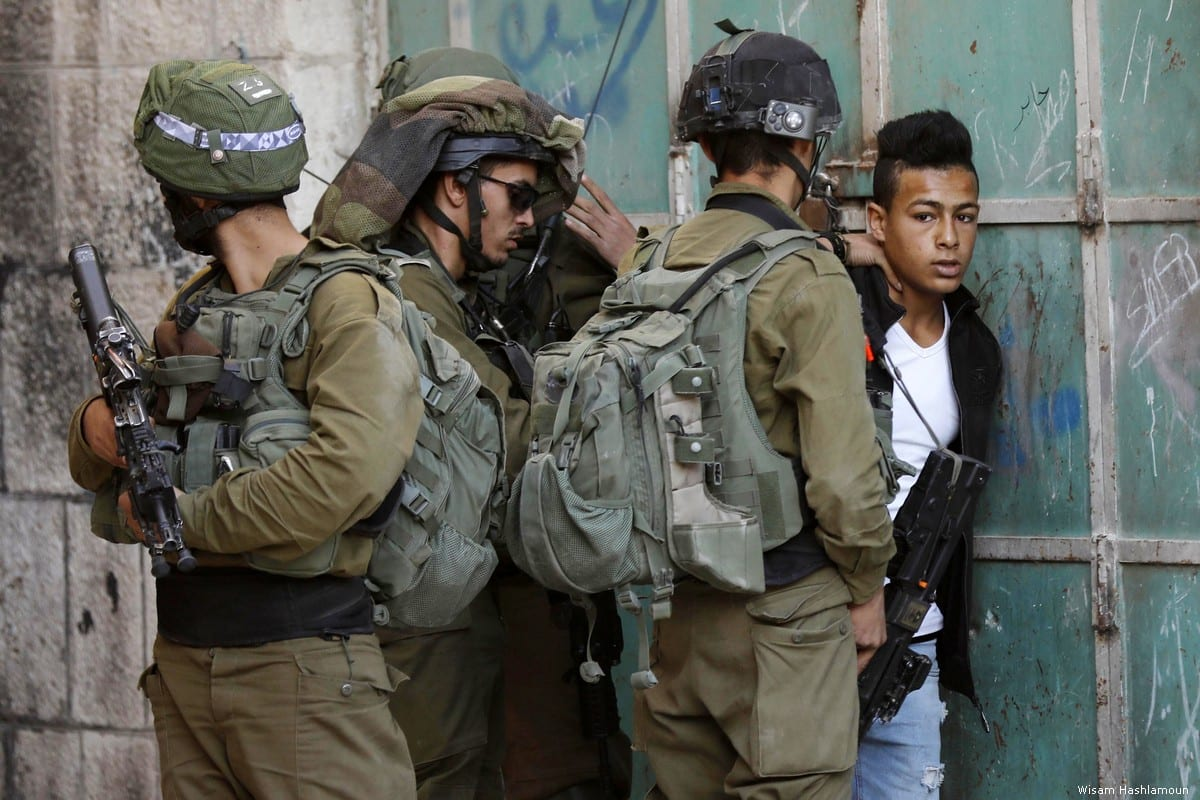 Israeli forces detain a Palestinian youth during a raid in the Old city of the West Bank city of Hebron on November 2, 2018. [Wisam Hashlamoun]