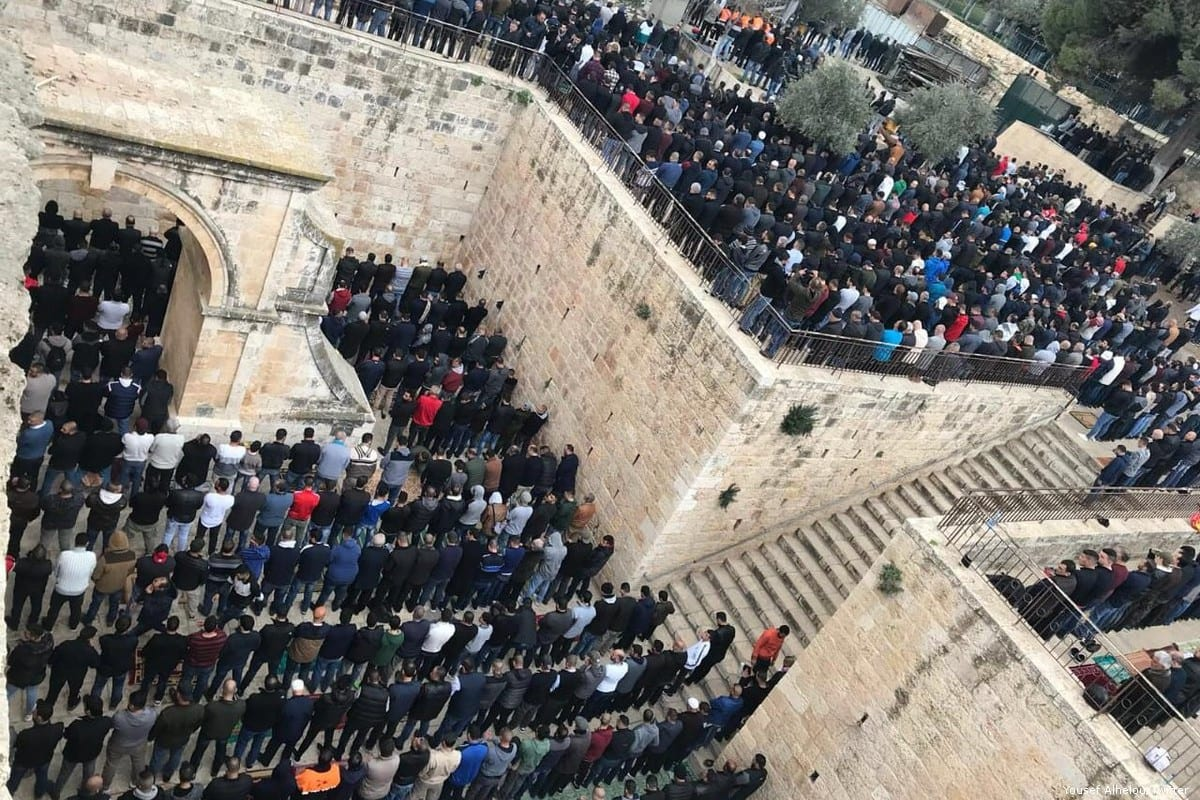 Palestinians perform prayer in front of Al-Rahma Gate (Gate of Mercy) of Al-Aqsa Mosque Compound, as Israeli security forces stand guard behind them after Al-Rahma Gate was chained by Israeli police in Jerusalem on 20 February 2019 [Faiz Abu Rmeleh/Anadolu Agency]