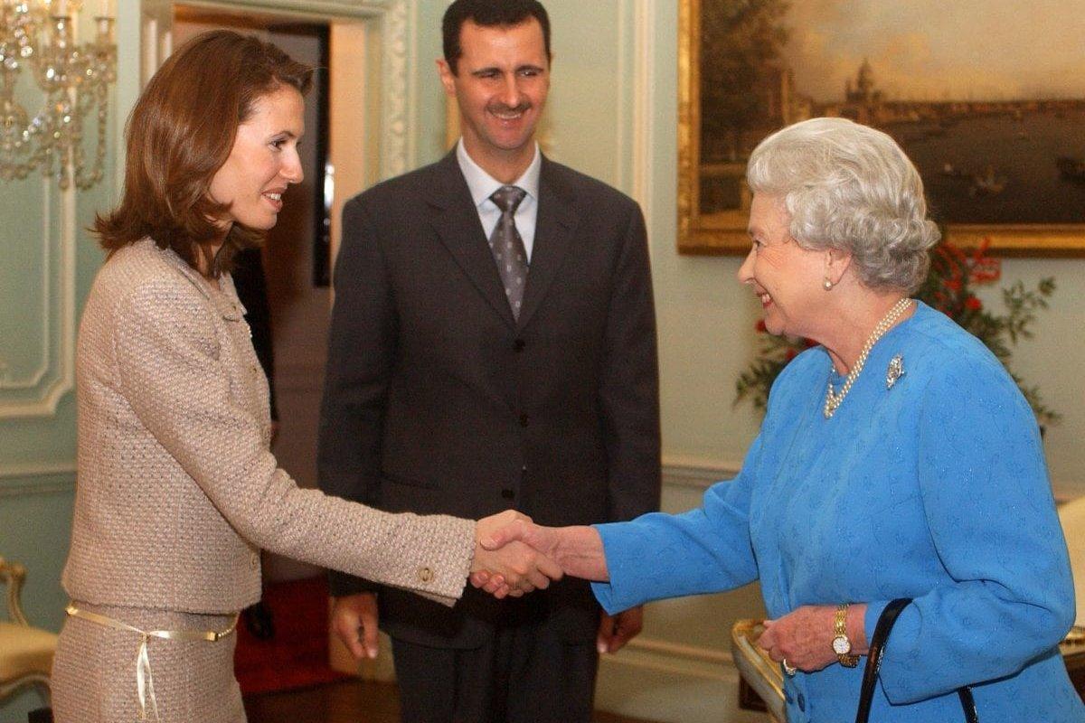 Queen Elizabeth II receives Asma Al-Assad and her husband, the President of Syria Bashar Al-Assad, 17 December 2002, at Buckingham Palace, in London. [KIRSTY WIGGLESWORTH/AFP/Getty Images]