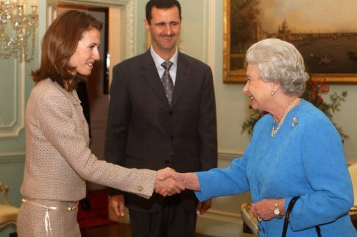Queen Elizabeth II receives Asma Al-Assad and her husband, the President of Syria Bashar Al-Assad, 17 December 2002, at Buckingham Palace, in London. [KIRSTY WIGGLESWORTH/AFP/Getty Images]