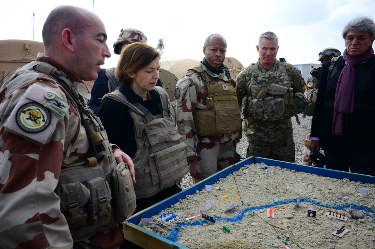 (L to R) French Major of the Wagram Task Force Francois-Regis Legrier explains military positions on a sand map to French Defence Minister Florence Parly, French General Jean-Marc Vigilant, US Army General Paul La-camera, and French ambassador to Iraq Bruno Aubert, at a French artillery forward operating base (FOB) near al-Qaim in Iraq's western Anbar province opposite Syria's Deir Ezzor region, a few kilometres away from the last scrap of territory held by IS, on 9 February 2019. [DAPHNE BENOIT/AFP/Getty Images]