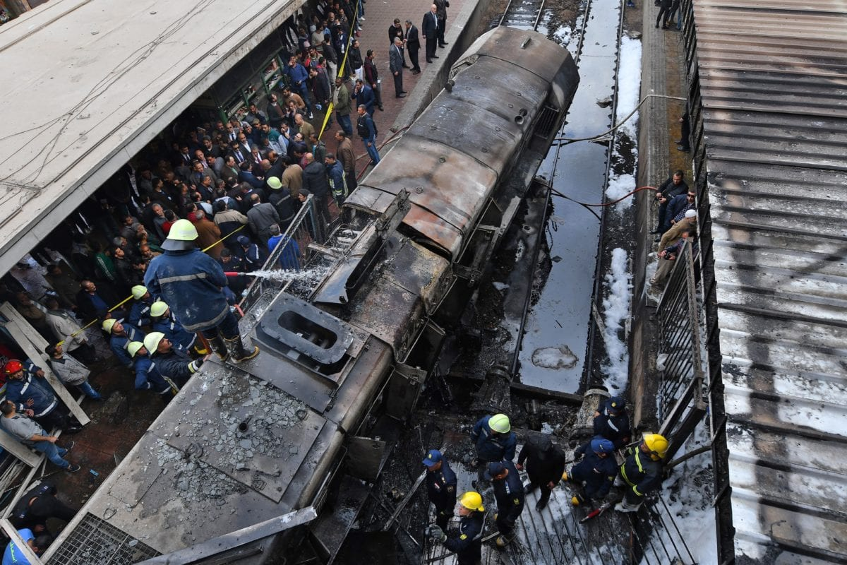 Fire fighters and onlookers gather at the scene of a fiery train crash at the Egyptian capital Cairo's main railway station on February 27, 2019. - The crash killed at least 20 people, Egyptian security and medical sources said. The accident, which sparked a major blaze at the Ramses station, also injured 40 others, the sources said. [STRINGER / AFP/Getty Images]